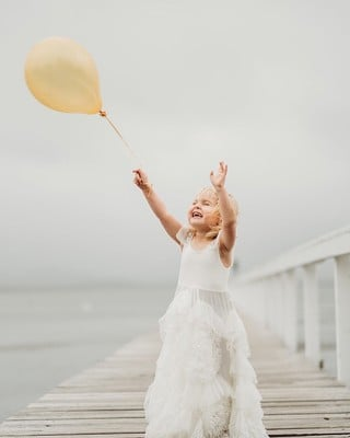 Penny in a white dress on a pier chasing a yellow balloon